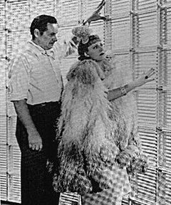 Between the scenes of Columbia´s THEODORA GOES WILD, Irene Dunne examines a new decorating invention, glass bricks, with director Richard Boleslawski