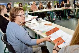 Die SPD-Landtagsabgeordnete Silke Lesemann verteilt in der Klasse E1 eine Broschüre zum Thema Migration und Asyl. (Kühn/haz)