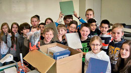 In dieser Kiste steckt allerhand drin: Eine fünfte Klasse der KGS freut sich über die neuen Unterrichtsmaterialien. Die alten liegen noch im gesperrten O-Trakt und sind nach dem Großbrand nicht mehr brauchbar. (Gückel/HAZ)