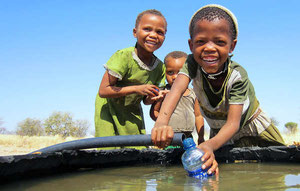 Niñas bosquimanas disfrutan del agua del pozo de Mothomelo. © Survival