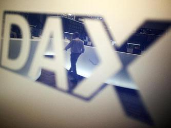 Ein Börsenhändler spiegelt sich im Logo des Deutschen Aktienindexes (DAX). Foto: Fredrik von Erichsen