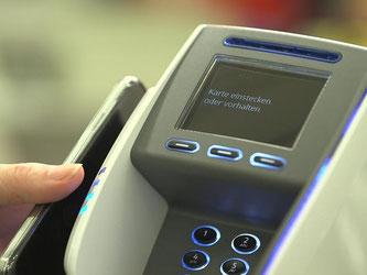 NFC-fähige Handys müssen zum Bezahlen einfach nur kurz ans Terminal gehalten werden. Foto: GS1 GmbH/Marcus Meertz