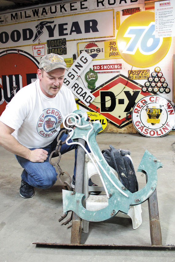 """Brian """"Beaver""""Kueter works on the old neon sign from former Anchor Inn inBellevue."""