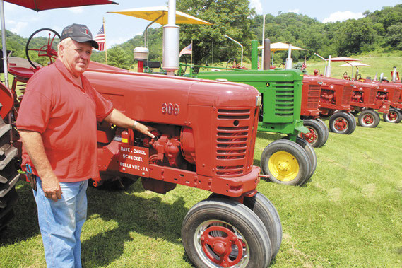 Dave Scheckel is pictured here on Mill Creek Road with 17 classic tractors he has restored over the decades.