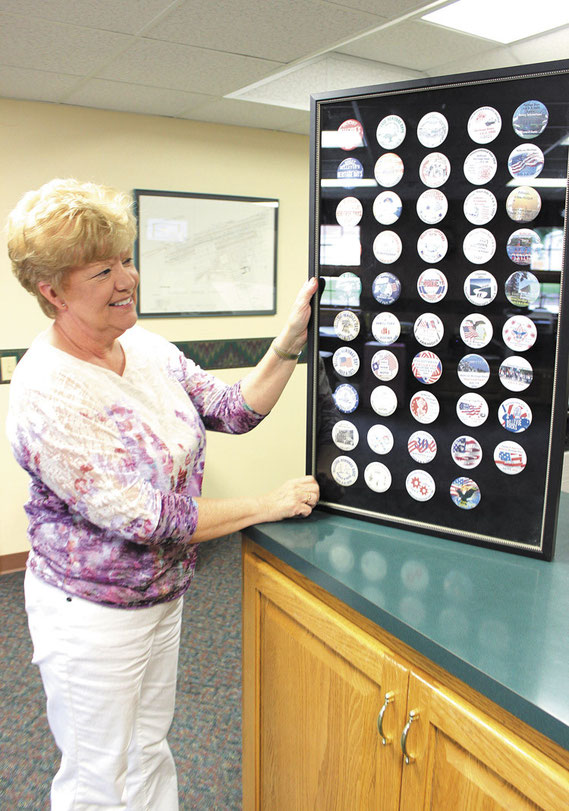 Bellevue City Clerk Janet Callaghan shows off her collection of Heritage Days Buttons that date back to the early 1960s.