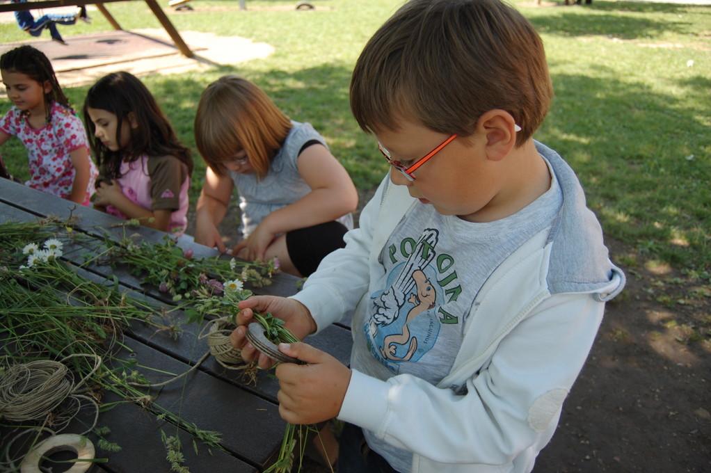 Federico inizia ad avvolgere le erbe sulla base di legno...