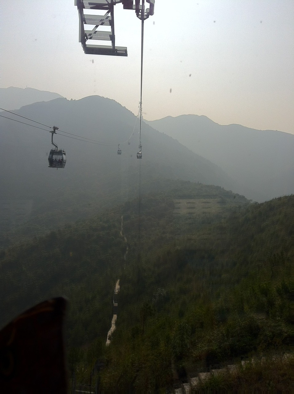 This is actually the longest single cable car ride I've been on ... and I live in Switzerland! It doesn't simply go up one mountain, it travels across them ... — at Ngong Ping Cable Car.