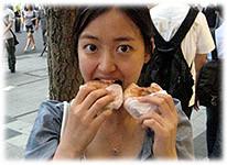 Picture of a young Korean woman eating donuts - Bild einer jungen Koreanerin beim Donuts essen