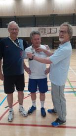 Penningmeester Jan Mossink (R) hangt Frits Hartman (L) en Wil Zwang het coachfluitlintje om op de dag van de coaches.