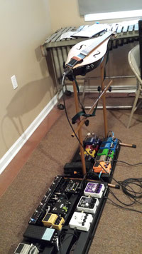 Photo of Sam Edelston's Rod Matheson electric dulcimer, on a stand, with two pedalboards underneath.