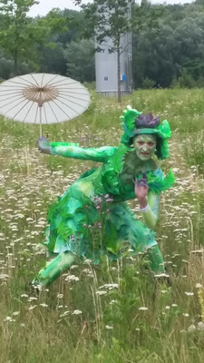 Maike Bartz posiert im Distelkostum mit weißem Schirmchen in einer Wiese, in der Schafgarbe blüht.