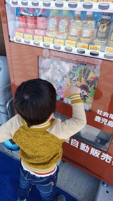 自動販売機でジュースを買う子供の写真