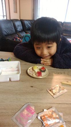 お菓子を見つめる子供の写真