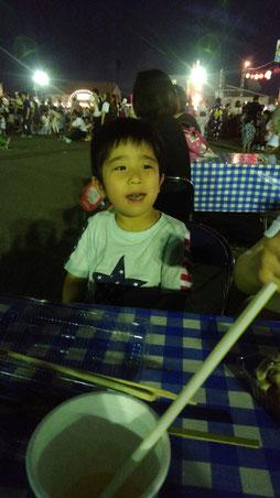子供が夏祭りで食べ物を食べる写真
