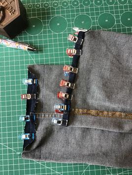 des pinces de couture maintiennent l'ourlet d'un jean