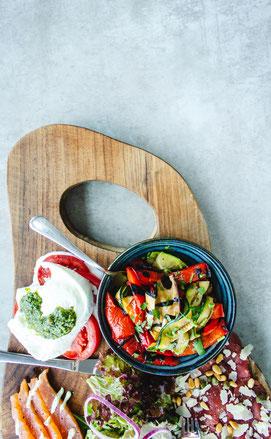 Viel buntes Gemüse, Antipasti und eine Auswahl an Salaten auf einem Holzbrett