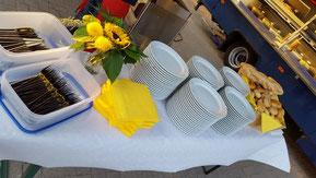 Geschirr und Besteck, werden mit Servietten und einem Brotkorb auf einem Tisch bereit gestellt.