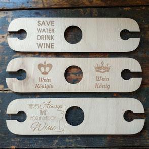 Drei Weinflaschen- und Glashalter mit unterschiedlichen Gravuren.