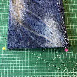 épingles apposées sur le bas d'un pantalon jean