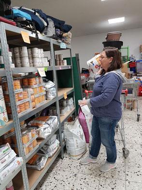 Frau räumt Futter in ein Regal mit medizinischem Sonderfutter