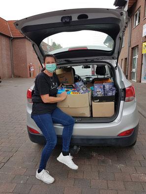 Frau mit Kofferraumladung voller Tierfutterspenden.