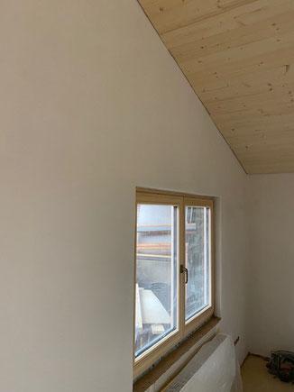 Innenausbau mit Lehm und Holz. Wände mit mineralischem Lehmputz. Weiße Farbgebung durch Lehmfarben. Deckenbekleidung Fichte Nut und Feder unbehandelt.