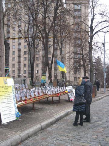 Menschen an der Gedenkstätte für die am 20. Februar 2014 in Kiew erschossenen Maidananhänger auf der Institutska Straße, im Hintergrund das Hotel Ukraina