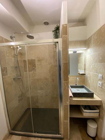 Salle de bain en travertin depuis la chambre, avec douche italienne effet pluie tropicale