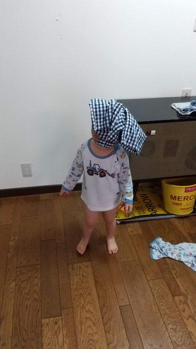 ズボンを頭からかぶる子供の写真