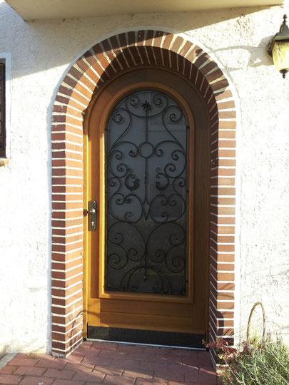 Rundbogen-Haustür aus Eiche, passend zu einem alten, schmiedeeisernem Gitter, gefertigt.