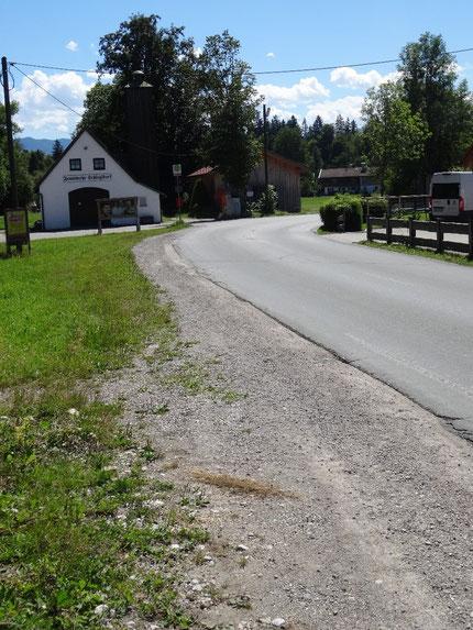 Straßenbankett mit Blick auf eine Kurve und einem altem Feuerwehrhaus