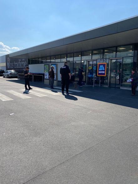 とあるスーパー。店内に入る人数が決まっているので前の人が終わるまで並んで待ってます。待つ間も1メートル間隔を開けて待っています。