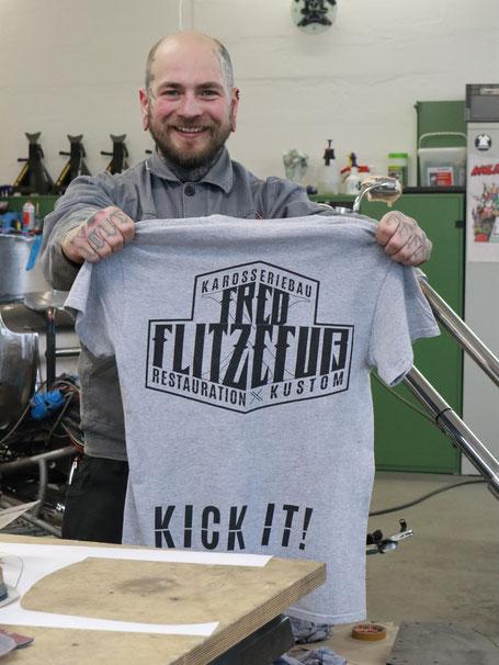 Max hält das Shirt mit neuem Logo für sein Merchandise in der Hand. Projekt: Logo Redesign for Fred Flitzefuß Custom. By Zuni from BRAVE & BUTT DESIGN STUDIO