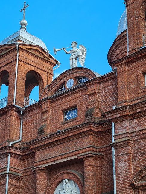 Nuo bažnyčios stogo trimituoja Arkangelas Mykolas