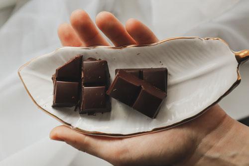 Eine Frau hält eine weiße Schale mit Zartbitterschokolade in der Hand