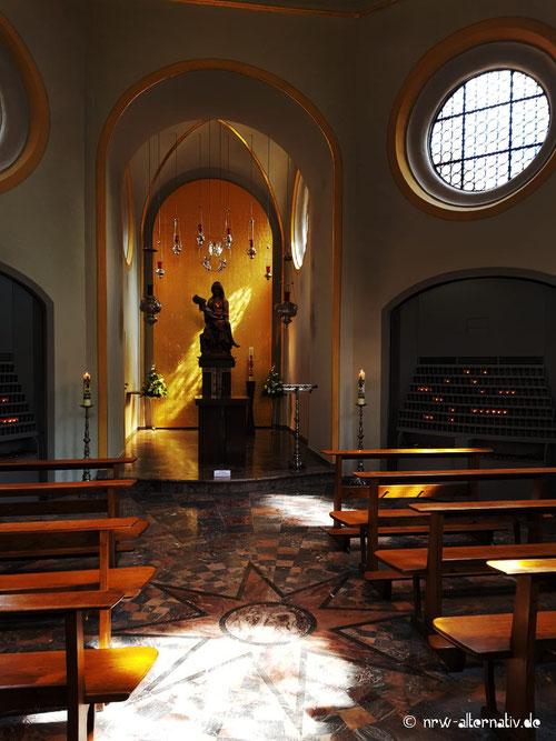Hier zu sehen: Das Gnadenbild von Maria in Telgte, eine Kirche und brennende Kerzen.