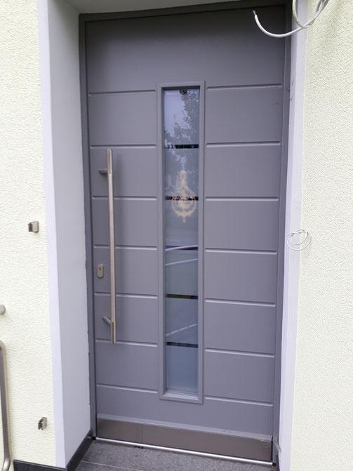 Moderne Haustür mit Ziernuten, sandgestrahler Scheibe, Edelstahlbeschlägen, und motorisch betätigter Mehrfach-Verriegelung