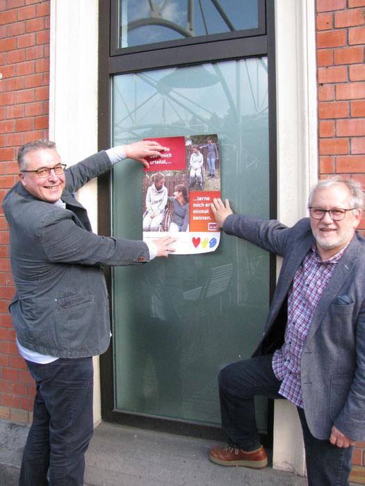 Teilhabeberater Günther Weinz (rechts) beim Aufhängen eines Plakates; Caritas-Dienststellenleiter Harald Pillny assistiert ihm dabei
