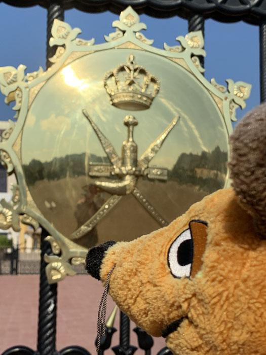 Um den Palast herum sind auf goldfarbenen Schilden die Insignien der Macht des Sultans abgebildet.