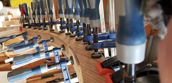 Die Rahmen des Schaukelstuhles bestehen aus verleimten KAstenprofilen. Die Teile fügen sich leicht in Falzverbindungen. Viele Klemmen sorgen beim Verleimen für eine gleichmäßige Druckverteilung.