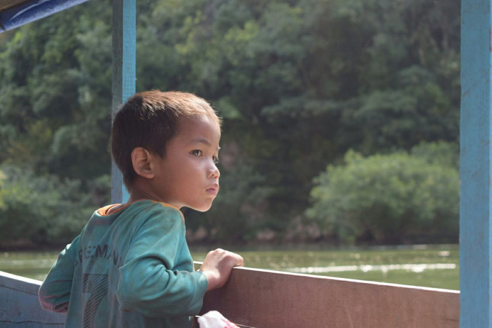 渡船の欄干を握る少年(ラオス)