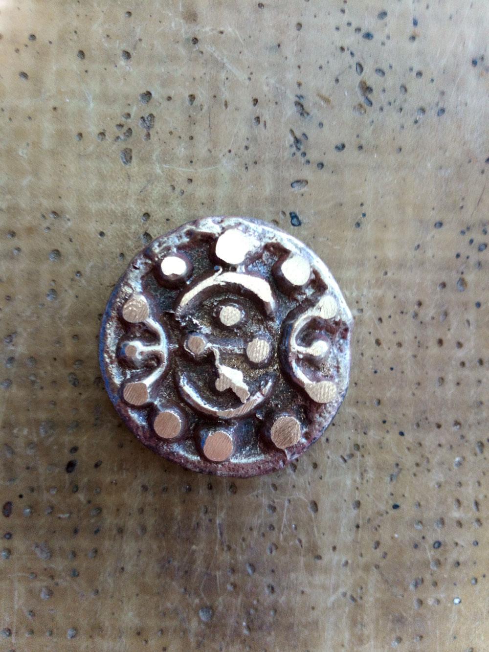 Peup a peu le talisman apparaît, toujours il comporte les formes du gui.