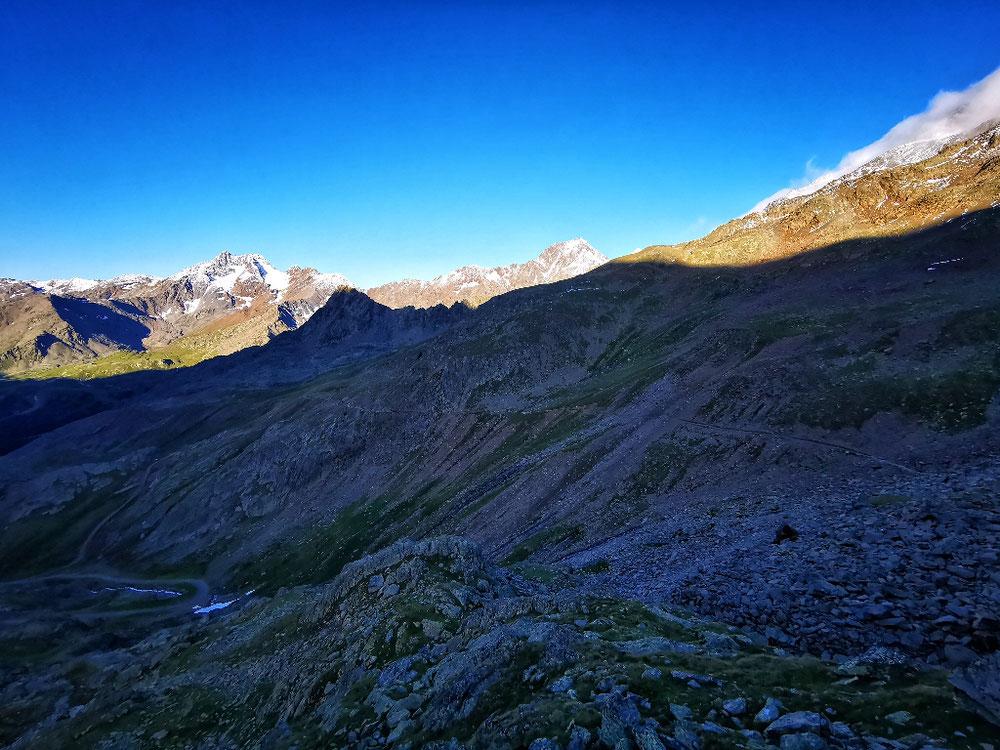 Der Abstiegsweg liegt noch im Schatten der hohen Berge