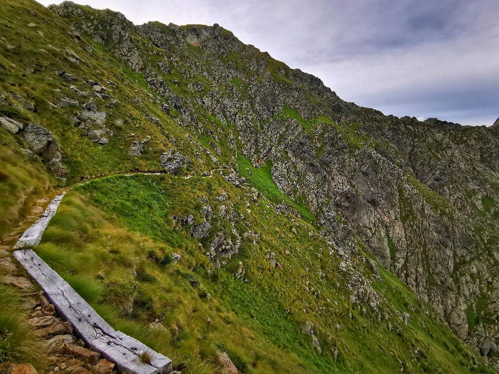 Über lange Holzbalken zieht der Weg am Hang entlang...
