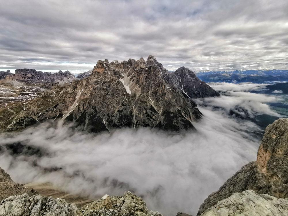 Eine dicke Wolkendecke liegt unterhalb des Gipfels
