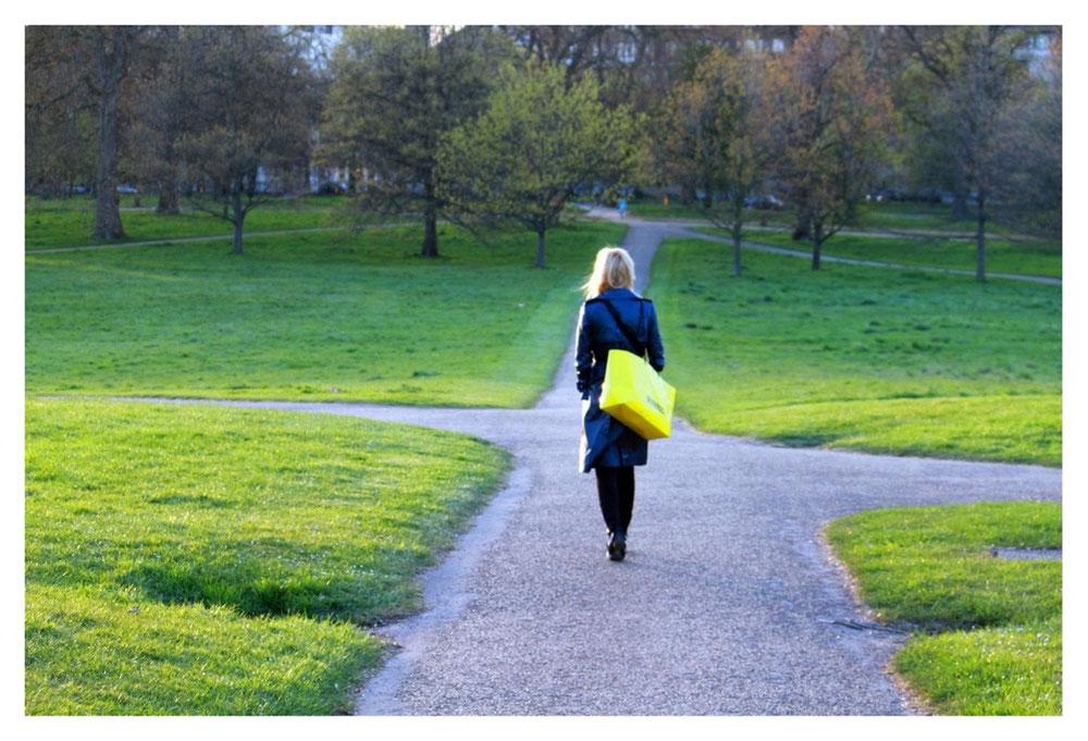 Eine Frau geht auf einem asphaltiertem Weg in einem Park spazieren.
