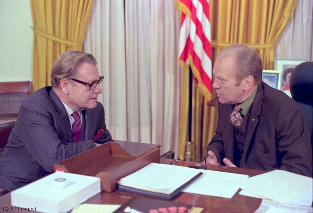 نائب الرئيس نيلسون روكفلر، إلى اليسار، والرئيس جيرالد فورد، يتشاوران في المكتب البيضاوي بالبيت الأبيض في العام 1974 (© AP Images)