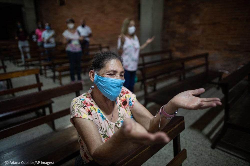 عدد من الناس يشاركون في قداس إلهي يوم 16 آب/أغسطس في كنيسة في كاراكاس بفنزويلا، حيث تسببت جائحة كوفيد19 في زيادة الحاجة إلى المساعدات الإنسانية إلى حد كبير.  (© Ariana Cubillos/AP Images)
