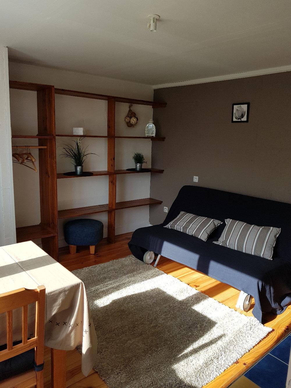 Salon avec canapé lit dans le studio
