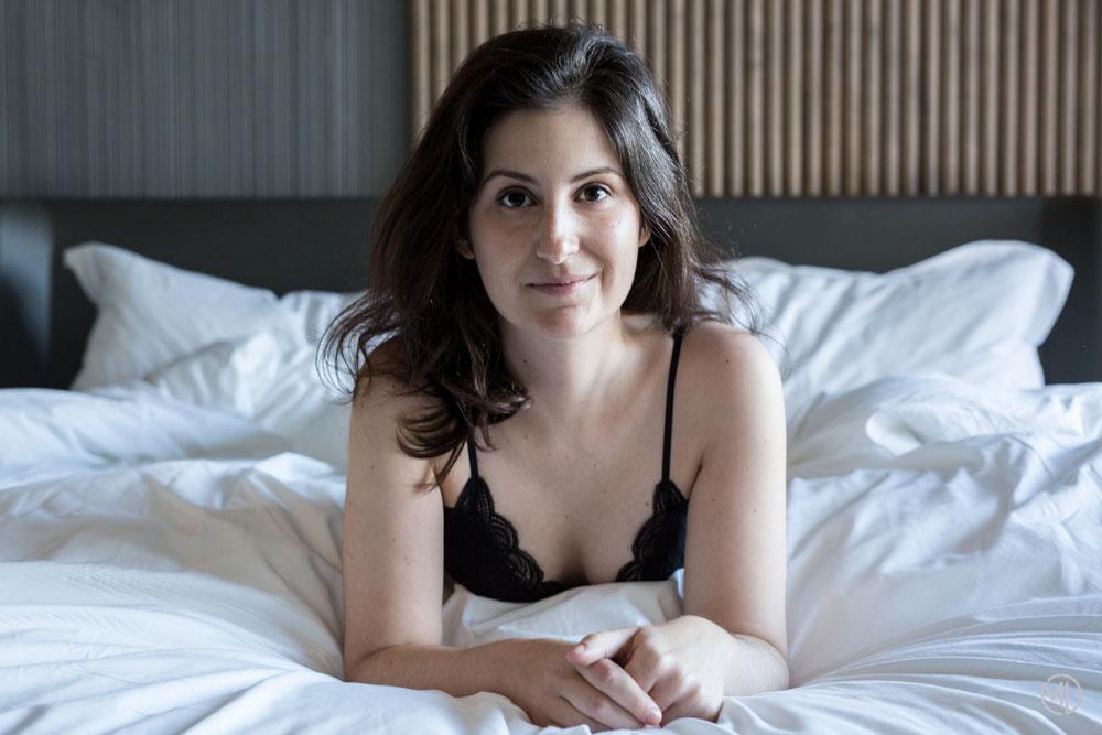 Photo boudoir femme blanche brune en sous-vêtements noirs sur le lit dans chambre d'hôtel à Montréal par Marie Deschene photographe